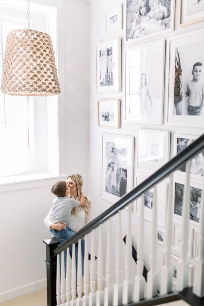 Stairway gallery with black and white family photos, black railing and mother and son exchanging a kiss