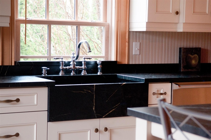 photo of a black soapstone countertop with a farmhouse style soapstone sink and a bridge faucet in front of a window