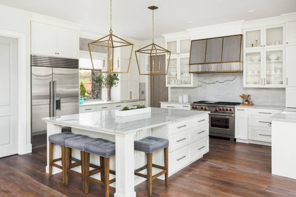 Picture of a white kitchen with mid-tine wood floors and a quartzite countertop and brass lanterns.