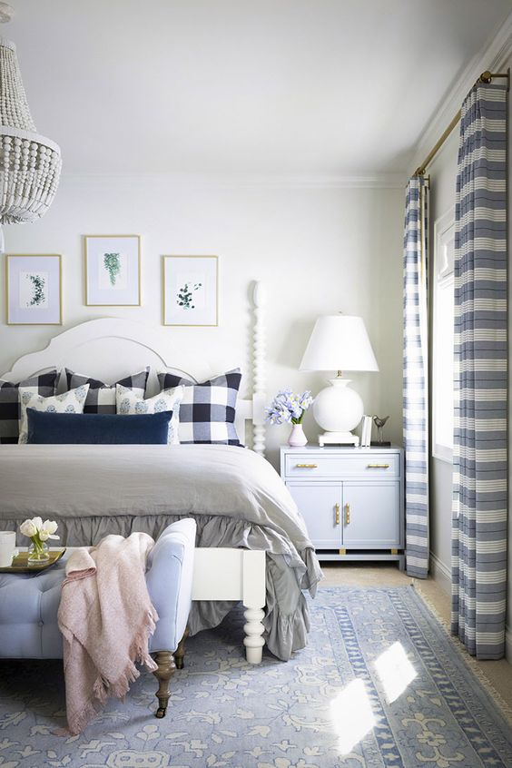 bedroom with blue and white drapes and traditional white spool bed