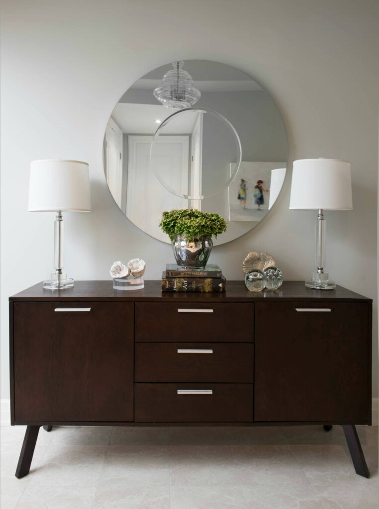foyer with cabinet, large round mirror and two lamps