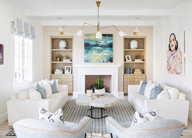 semetrical living room with whote sofas and blue accent pillows in front of a fireplace and built/in wall