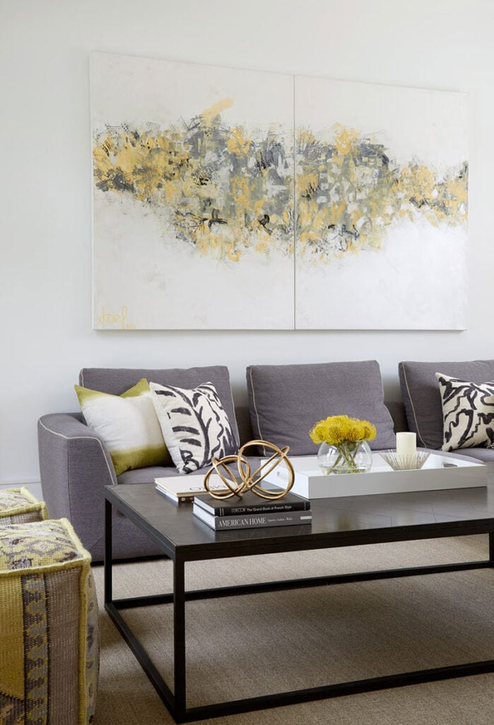 seating grouping in front of artwork in muted greys and pops of yellow