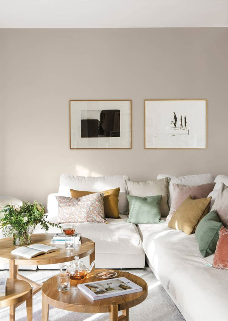white sectional with lots of accent pillows and three round nested coffee tables