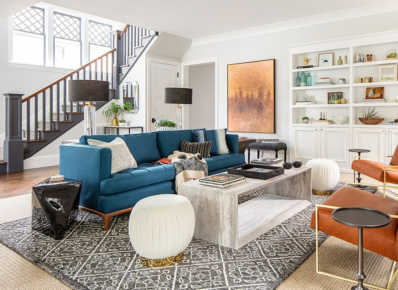 Living room with peacock blue sofa, stone coffee table, cognac leather chairs floating on a graphic rug