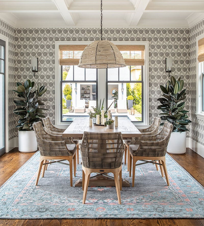 dining room with patterned wallpaper, and woven furniture and chandeleir on a blue rug