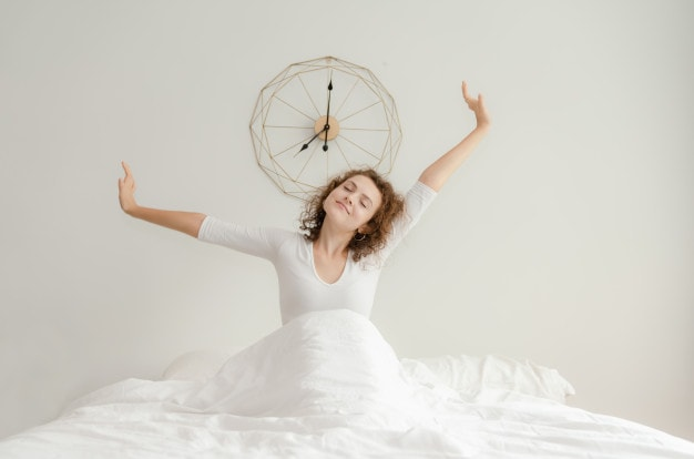 all white image of a woman enjoying a morning stretch before getting ou tof her bed dressed in white sheets
