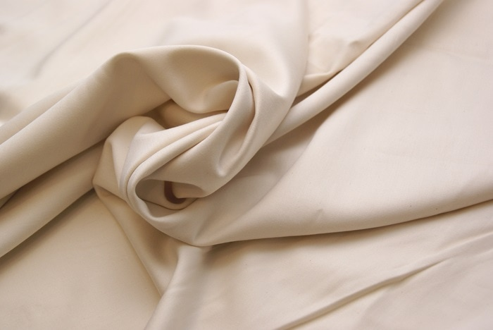 a swirl of fabric representing cotton sateen sheets in a soft almond colour