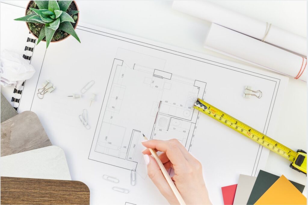 Designer's desktop with floor plan and measuring devices