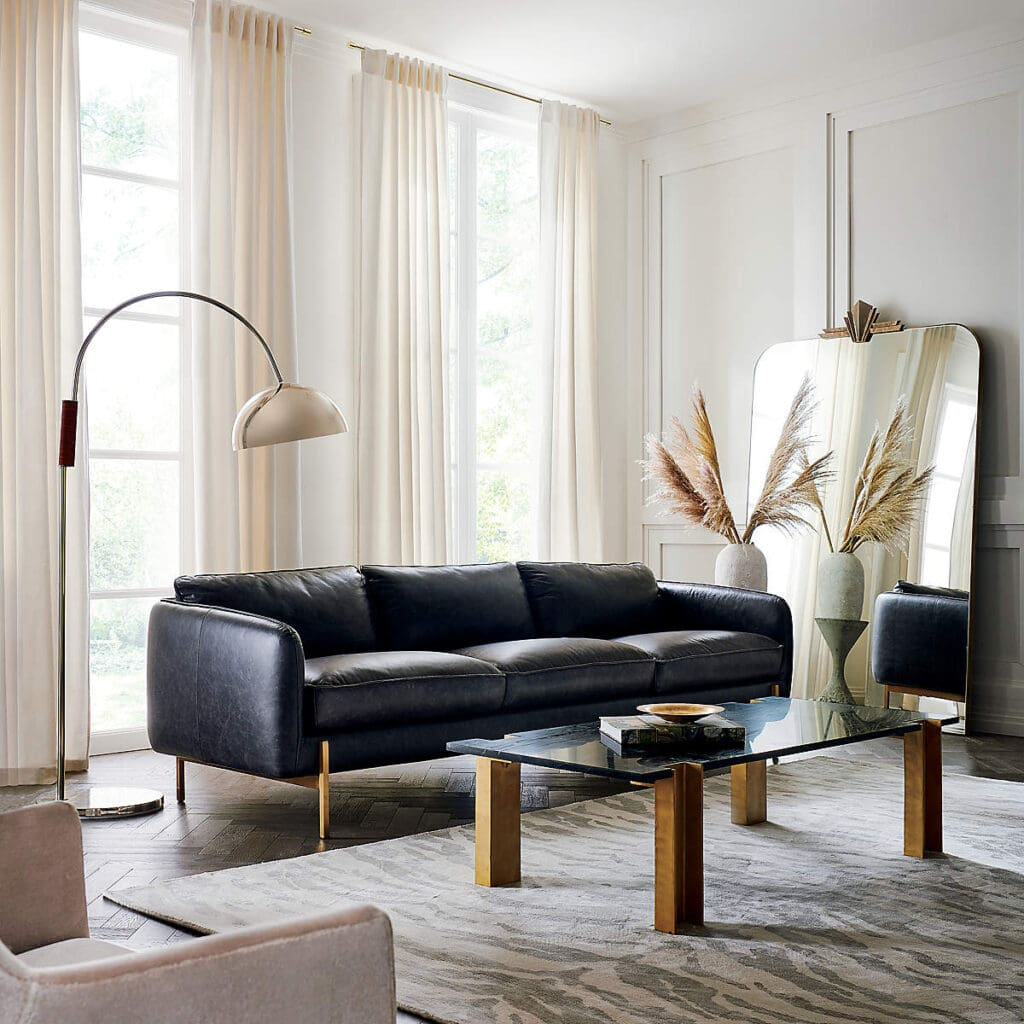 Sleek black leather 3 seat sofa with arc'd floor lamp in a white room with an oversized leaning mirror