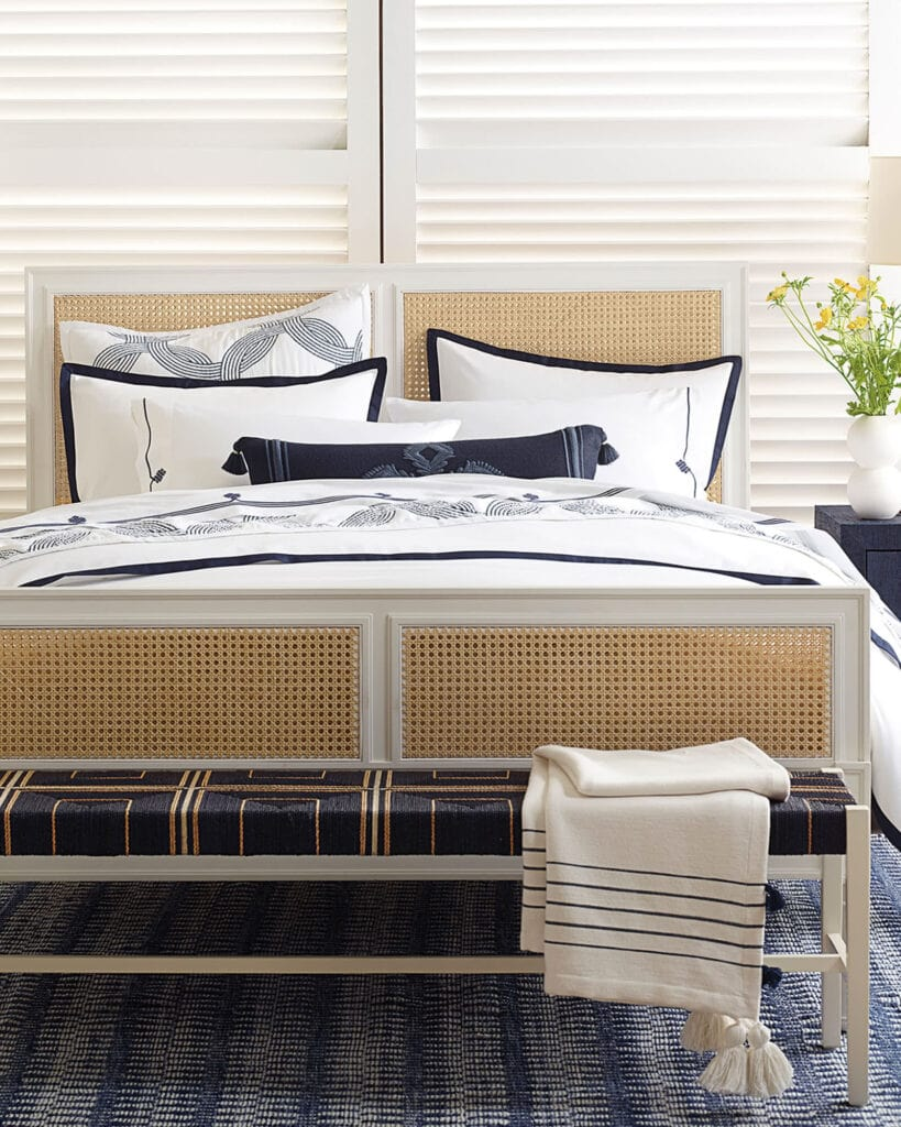 navy and white bedding on a white bed with caning inserts