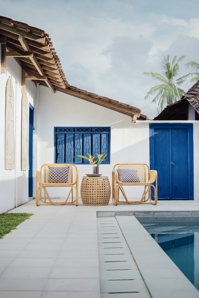 outdoor scene with 2 chairs next to a pool